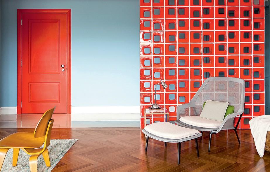 O contraste do azul com o vermelho é o que dá personalidade ao espaço. Além de disfarçar a porta do lavabo, os cobogós viabilizam a presença da poltrona – sem eles, o móvel ficaria fora de contexto na sala. Projeto da arquiteta Patrícia Martinez