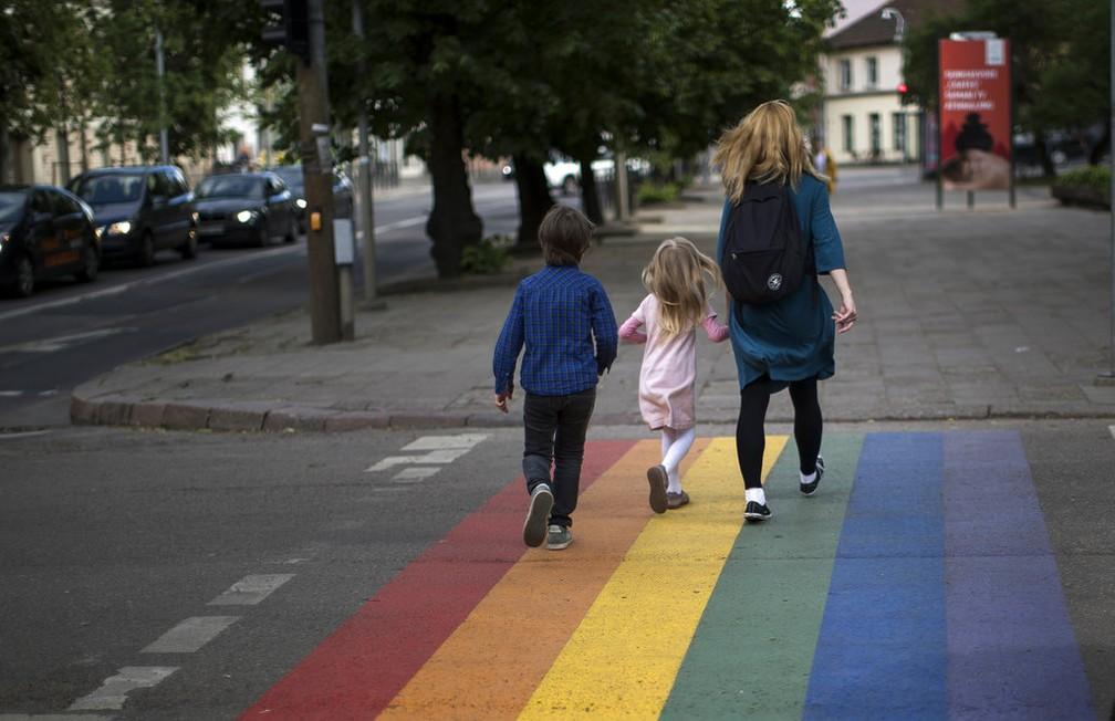 Uma mulher e uma criança caminham em um cruzamento de pedestres pintado nas cores da bandeira do arco-íris, um símbolo do movimento dos direitos dos homossexuais, para marcar o Dia Internacional contra Homofobia, Transfobia e Bifobia, em Vilnius, na Lituânia (Foto: Mindaugas Kulbi/AP)