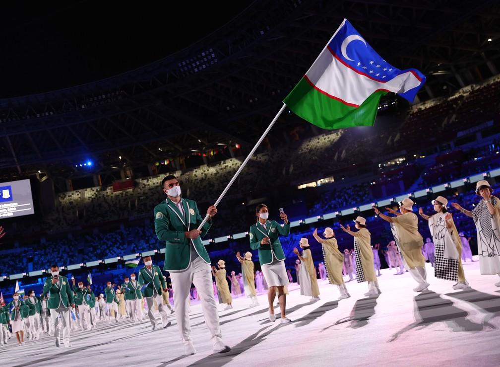 Bakhodir Jarolov carrega a bandeira do Uzbequistão durante a cerimônia de abertura dos Jogos Olímpicos de Tóquio, no Japão — Foto: Kai Pfaffenbach/Reuters