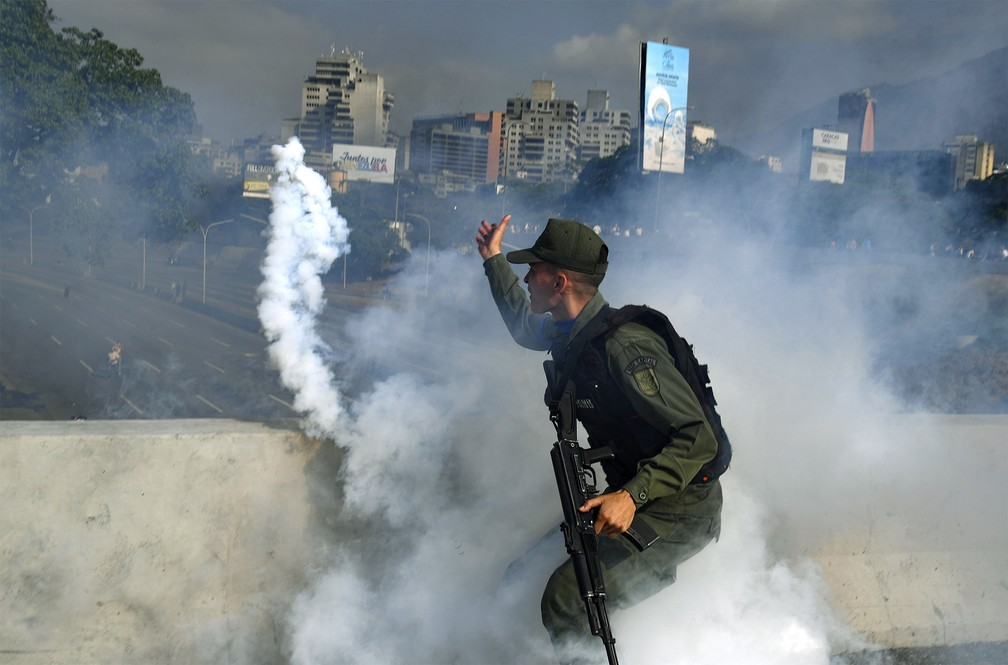 Militar apoiador de Juan Guaidó atira de volta uma bomba de gás lacrimogêneo durante confronto com forças leais a Nicolás Maduro — Foto: Yuri Cortez/AFP