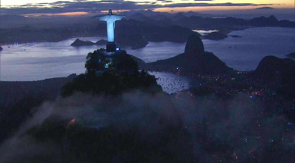 Imagem do Cristo Redentor já iluminado no fim da tarde  — Foto: Reprodução/ TV Globo
