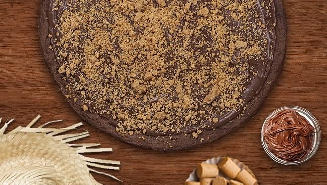 Pizza de massa de chocolate com cobertura de chocolate e paçoca