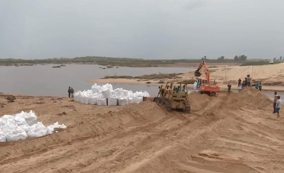 Lagoa da Paulista, em Carapebus, foi bloqueada com o uso de sacolas que suportam grande quantidade de areia para impedir que taboas cheguem às praias da Região dos Lagos — Foto: Reprodução/Inter TV