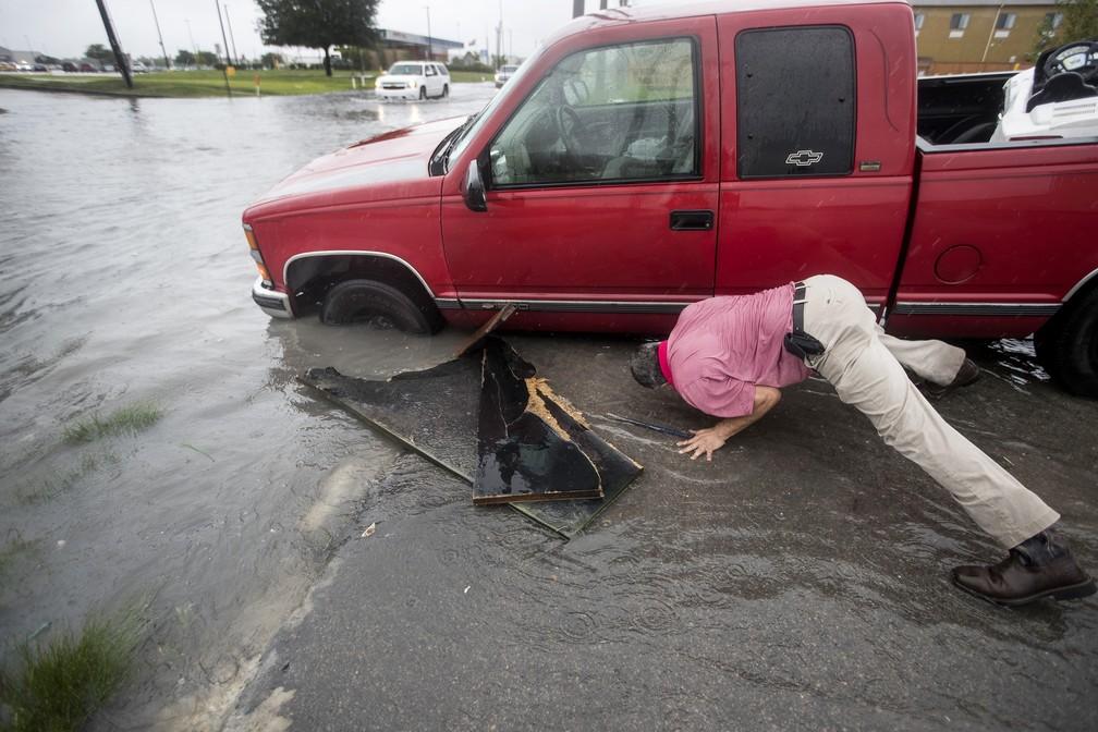 Na foto, um homem tenta tirar sua caminhonete de uma vala inundada depois da chuva causada pela tempestade tropical Imelda na terça-feira (17), em Houston, no Texas. — Foto: Brett Coomer/Houston Chronicle via AP