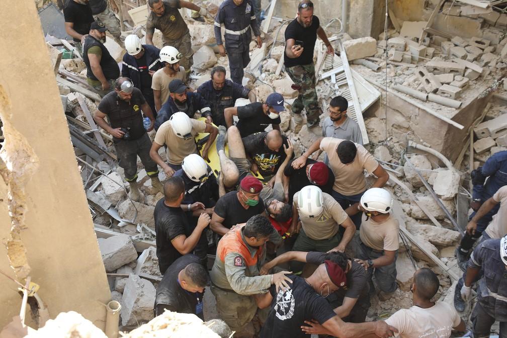 5 de agosto - Sobrevivente é retirado dos escombros após enorme explosão em Beirute, no Líbano — Foto: Hassan Ammar/AP