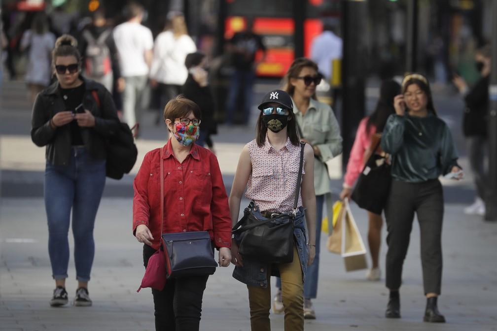 Algumas pessoas são vistas usando máscaras na Oxford Street em Londres, na Inglaterra, na segunda-feira (21) — Foto: Kirsty Wigglesworth/AP