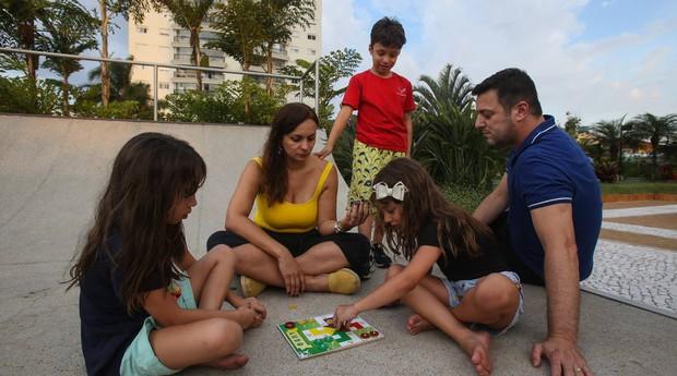 Adriane joga com os filhos. 'Se estivessem mexendo no celular, não iriam querer a companhia dos pais'  (Foto: Estadão Conteúdo)