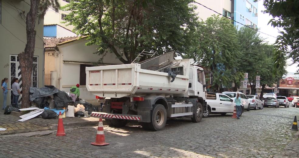 -  Dois caminhões e duas caminhonetes retiraram os materiais da residência em Divinópolis  Foto: Reprodução/TV Integração