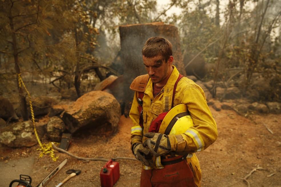 Bombeiro descansa em meio a floresta queimada no incêndio Camp Fire, na California — Foto: John Locher/AP Photo