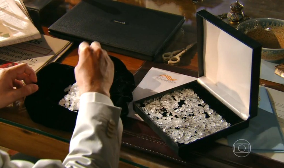 Alberto (Igor Rickli) coloca pedras de sal nos diamantes que Cassiano (Henri Castelli) levará para o Caribe — Foto: Globo