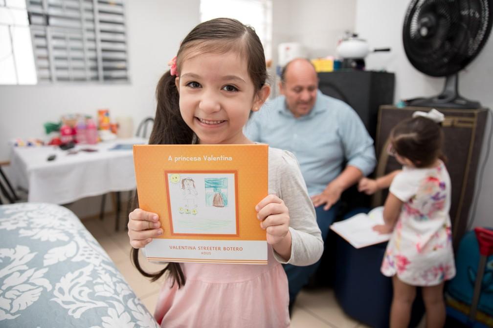 A colombiana Valentina Streeter Botero, de 5 anos, mostra o livro que escreveu como parte do projeto do Instituto Adus (Foto: Marcelo Brandt/G1)