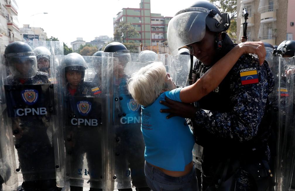 Manifestante é carregada por policial durante protesto contra Nicolás Maduro em Caracas, na Venezuela — Foto: Carlos Garcia Rawlins/Reuters