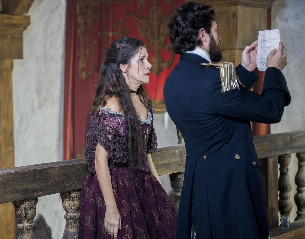 Elvira (Ingrid Guimarães) mostra a Thomas (Gabriel Braga Nunes) as investigações de Joaquim (Chay Suede) contra ele, em 'Novo Mundo' — Foto: TV Globo