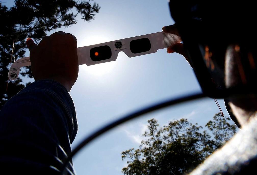 Uma mulher testa óculos especiais para o eclipse solar total em Coquimbo, no Chile. — Foto: Rodrigo Garrido/Reuters