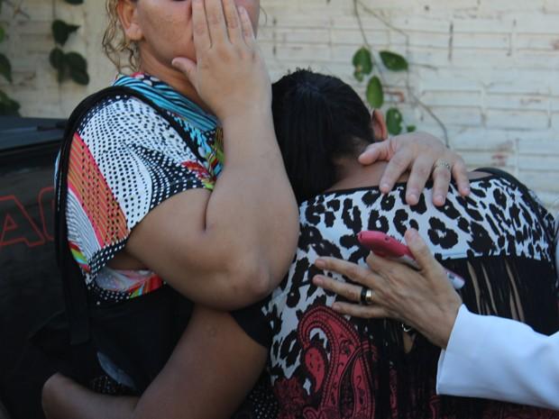 Mãe da garota é amparada por colegas na porta do hospital (Foto: Ellyo Teixeira/G1)