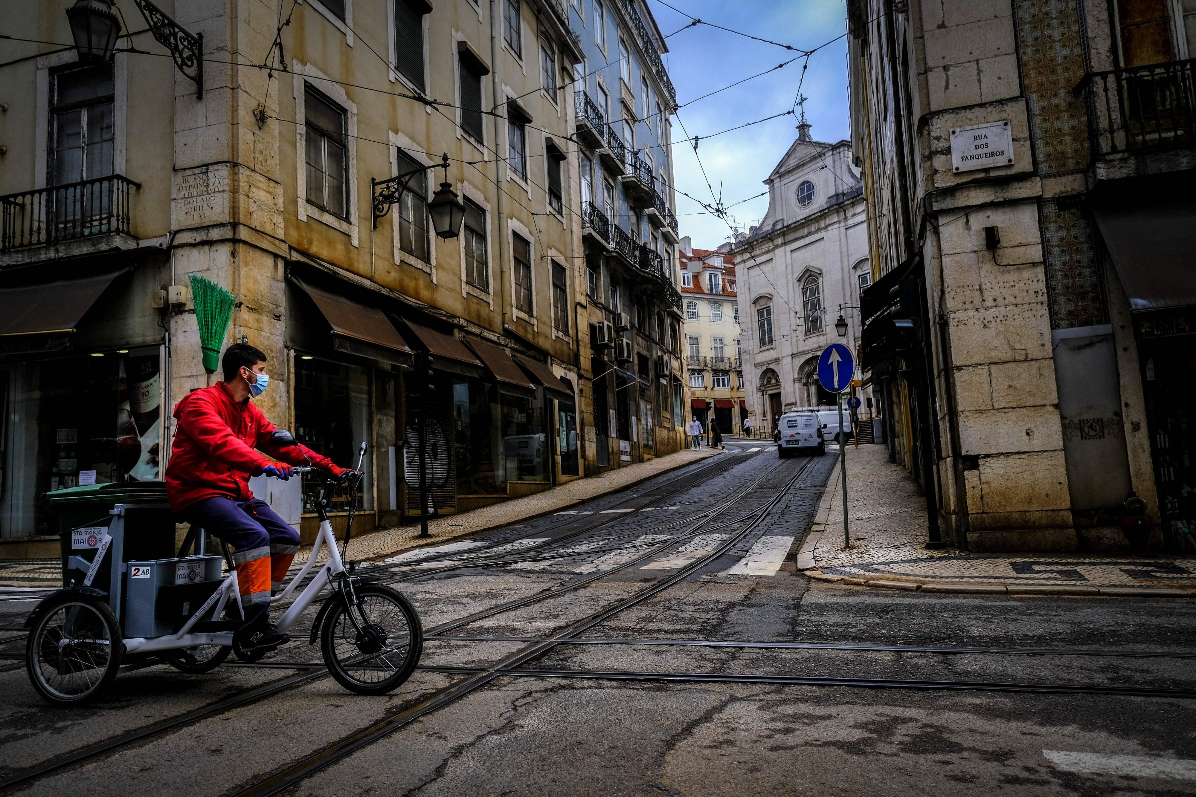 Homem guia bicicleta pelas ruas desertas de Lisboa, Portugal