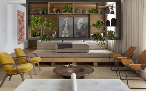 Apartamento tem estante flutuante que divide sala de estar e de TV