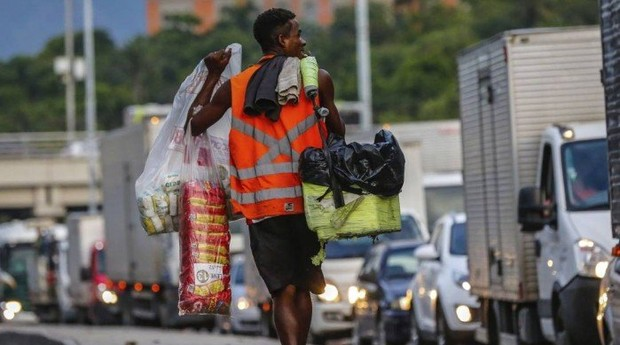 Com a mulher grávida, Robson Silva vende biscoitos na via expressa, monitorado por equipamento eletrônico preso à perna  (Foto: Reprodução/Agência O Globo)