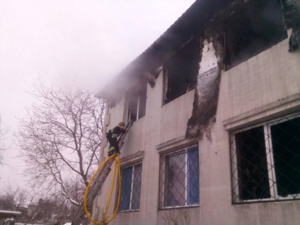 Socorrista tenta entrar pela janela da residência para idosos atingida por um incêndio na Ucrânia em 21 de janeiro de 2021 — Foto: Serviço de Emergência da Ucrânia/Reuters