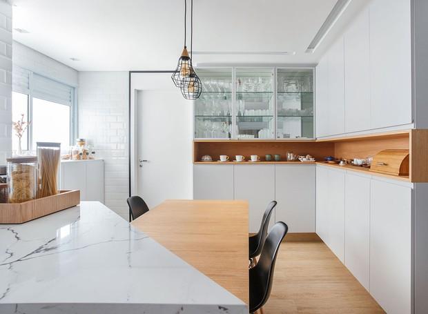 COZINHA | Na cozinha, há bastante uso de marcenaria, como os armários e uma bancada, da qual sai uma mesa de madeira. Eletrodomésticos da Viking. Louças e metais da Deca e da Mekal (Foto: Maura Mello/ Divulgação)