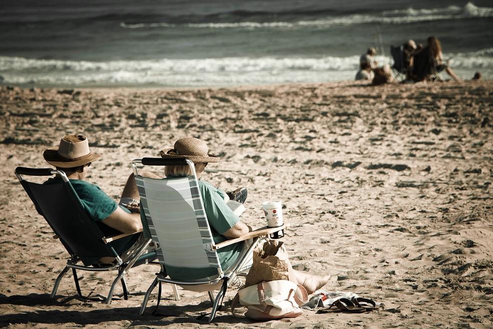 """Os """"novos velhos"""", entre 60 e 75 anos, são mais ativos e uma parcela considerável deste grupo tem renda superior à de gerações anteriores — Foto: https://commons.wikimedia.org/wiki/Category:Old_couples#/media/File:An_old_couple_relaxing_on_the_beach.jpg"""