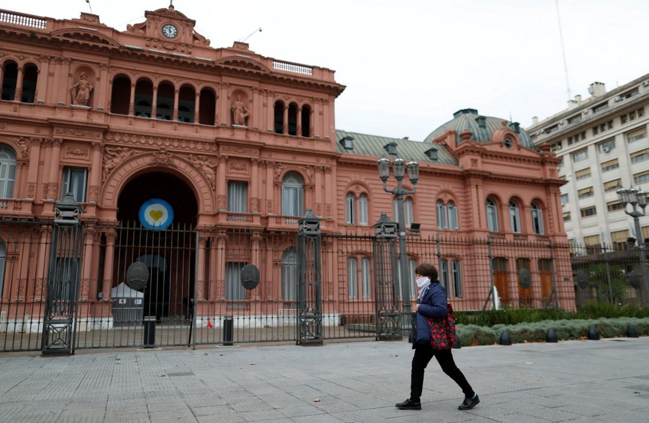 Na Argentina, mulher de máscara caminha em frente à Casa Rosada, palácio presidencial do país