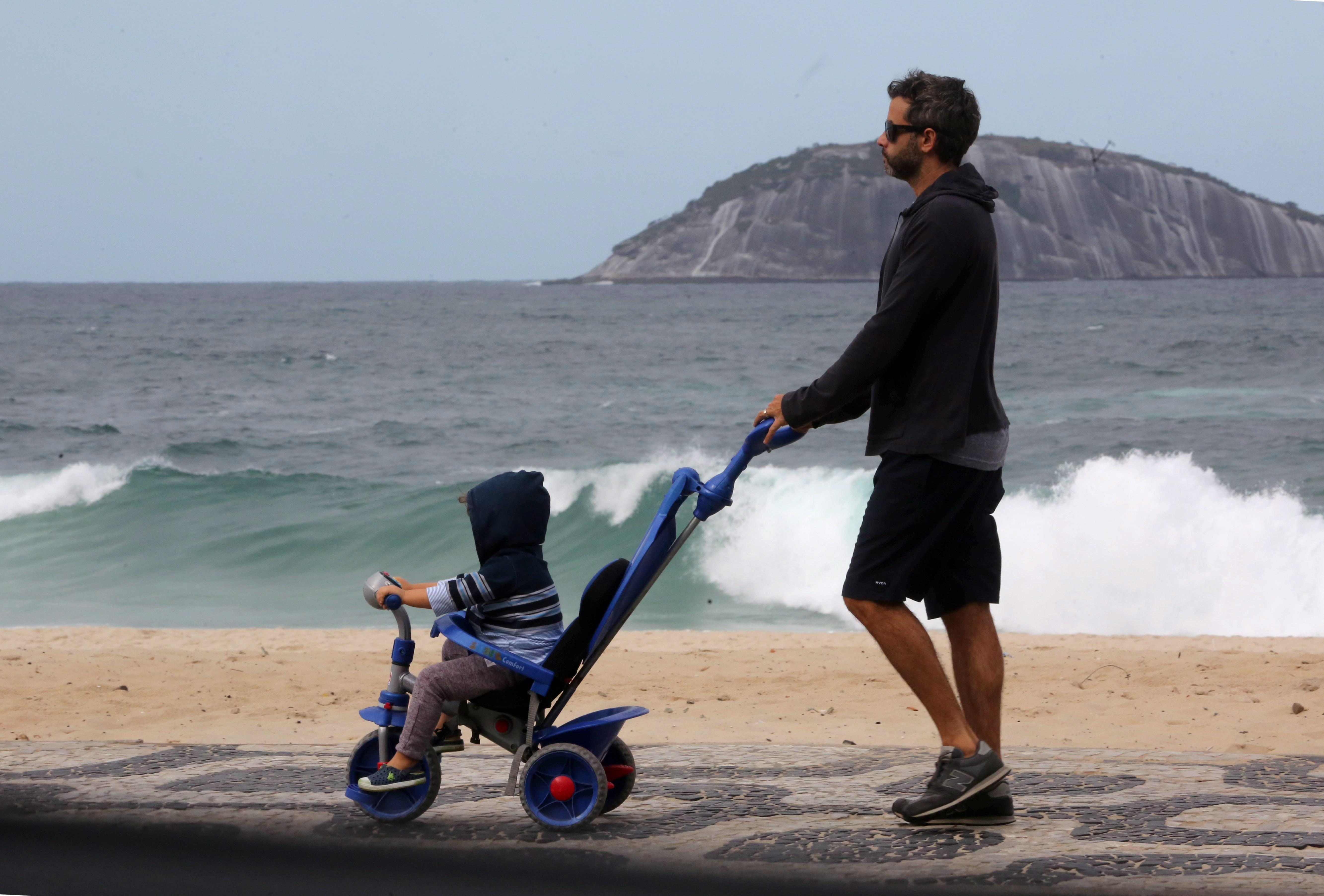 Homem empurra criança com velocípede na orla de Ipanema