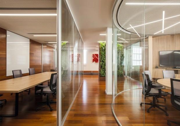 Jardim vertical, madeira e tons quentes resultam em escritório aconchegante