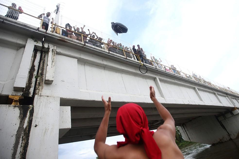 Migrante joga uma mochila da ponte que liga o México e Guatemala para evitar fronteira — Foto: REUTERS/Edgard Garrido