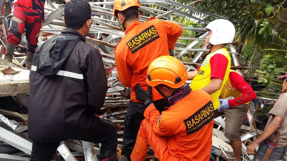 Equipe de resgate trabalha entre escombros na província de Baten após tsunami na Indonésia, na noite de sábado (22) — Foto: BASARNAS/via REUTERS
