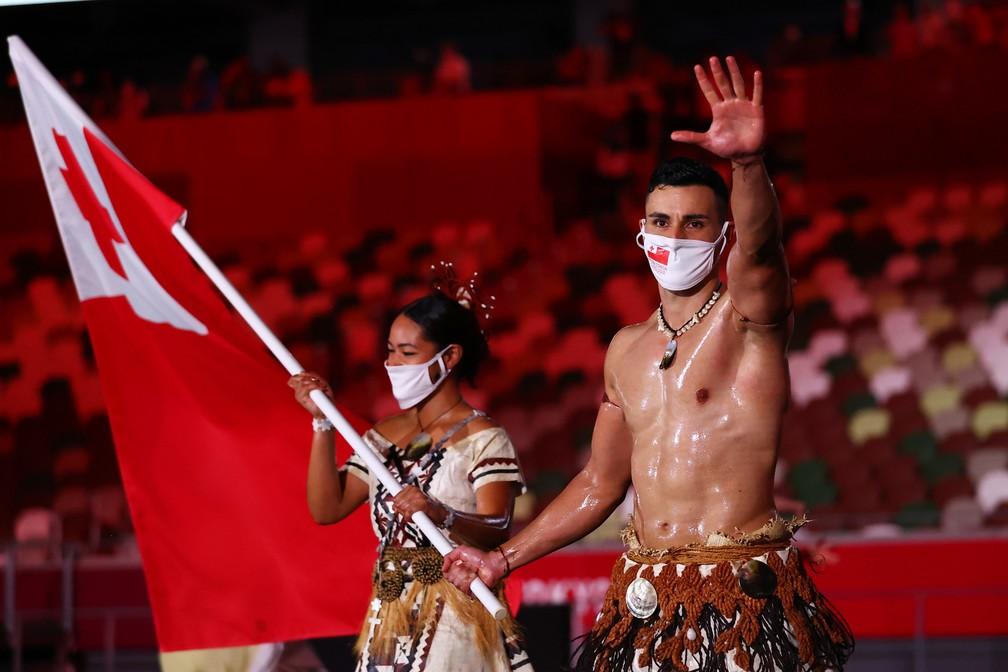 Malia Paseka e Pita Taufatofua, o 'besuntado de Tonga', levam a bandeira do país da Oceania  durante a cerimônia de abertura dos Jogos Olímpicos de Tóquio, no Japão — Foto: Stefan Wermuth/Reuters