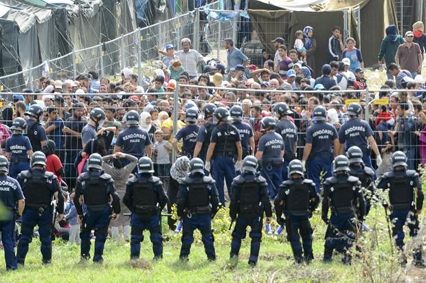 Policiais cercam acampamento para refugiados em Roszke, no sul da Hungria, depois de grupo com 300 deixar o local  (Foto: Stringer/ Reuters)