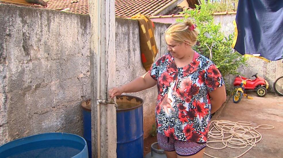 A dona de casa Jenifer Gomes guarda água em latões para dar banho nos filhos em Brodowski, SP (Foto: Ronaldo Gomes/EPTV)