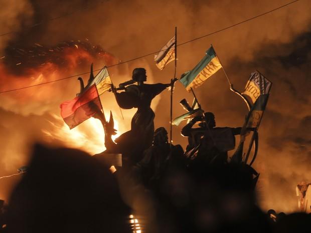 18/2 - Manifestantes colocam fogo em barricada durante confronto próximo ao monumentos aos fundadores de Kiev. (Foto: Efrem Lukatsky/AP)