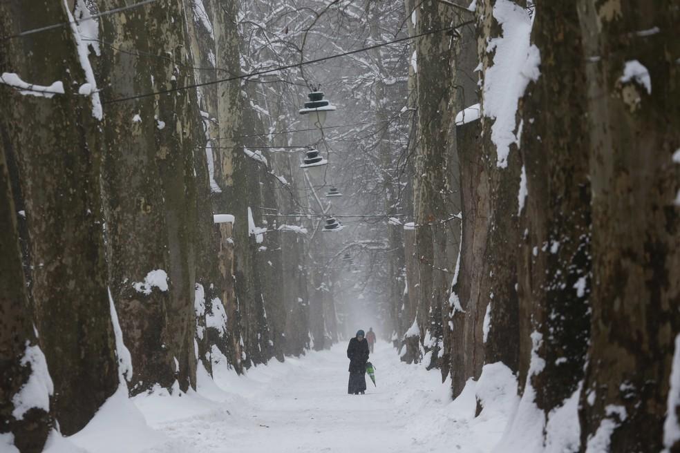 Mulher caminha sobre estrada coberta de neve em Sarajevo, na Bósnia (Foto: AP Photo/Amel Emric)