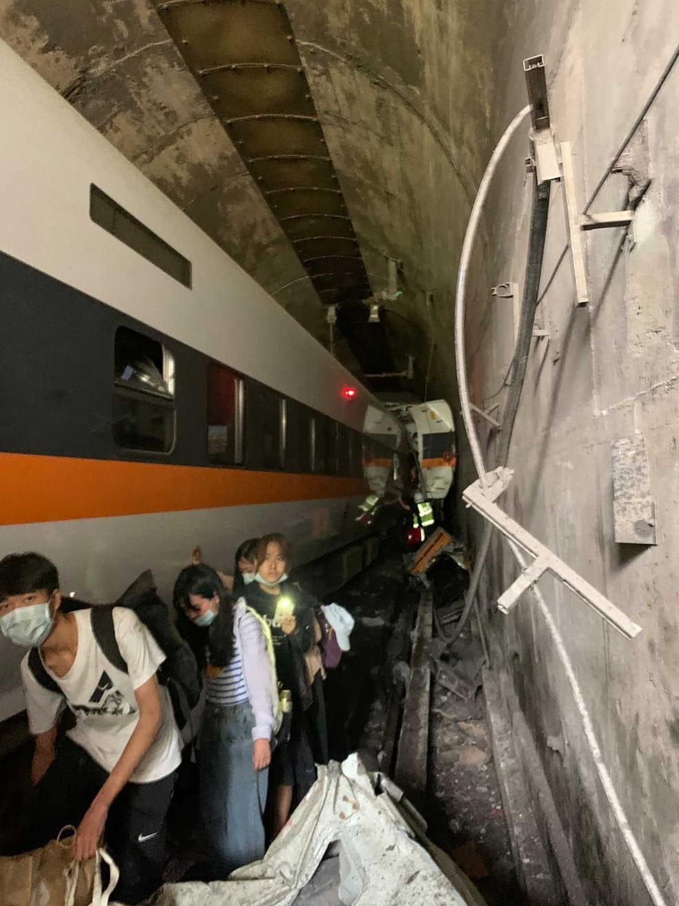 Equipes de resgate ajudam passageiros em trem descarrilado em Taiwan — Foto: Departamento Nacional de Bombeiros / via AP Photo