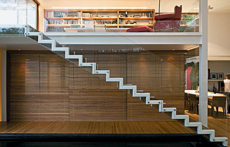 Leve e solta, a escada metálica dá acesso ao mezanino, onde fica a biblioteca protegida por guarda-corpo de vidro temperado. Embaixo, painéis deslizantes de madeira ripada fecham a cozinha. Projeto do escritório Bernardes Jacobsen