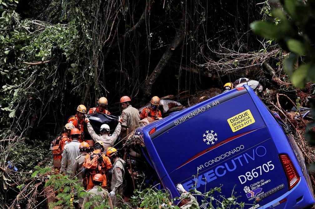 Bombeiros removem corpo encontrado em ônibus atingido por deslizamento na Avenida Niemeyer, no Rio de Janeiro — Foto: Ricardo Moraes/Reuters