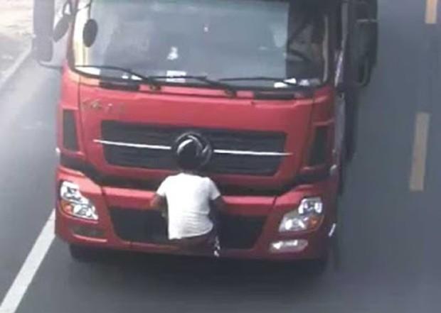 Motorista foi flagrado carregando amigo pendurado no para-choque dianteiro, com o objetivo de esconder a placa (Foto: Reprodução/YouTube/CCTV News)