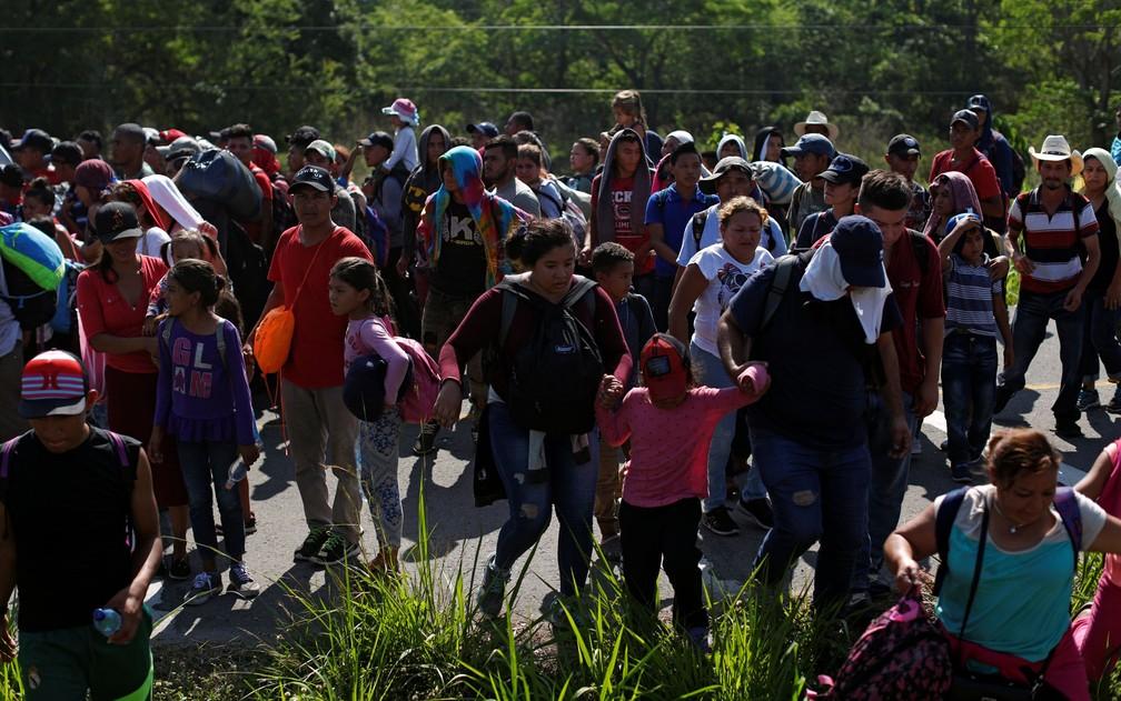 Migrantes hondurenhos caminham por Estrada em Metapa, no México, na sexta-feira (12) — Foto: Reuters/Jose Cabezas