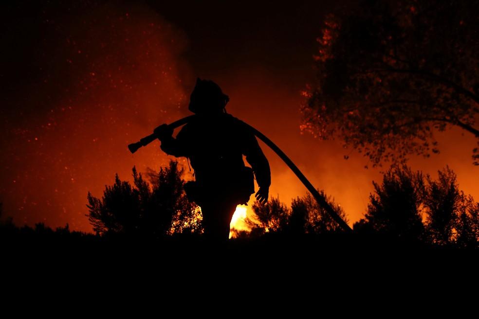 Bombeiro combate incêndio em Bonsall, na California, na quinta-feira (7)  (Foto: Mike Blake/ Reuters)