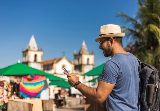 Homem usa celular em marco de Olinda, Pernambuco (Foto: Pollyana Ventura/Getty Images)