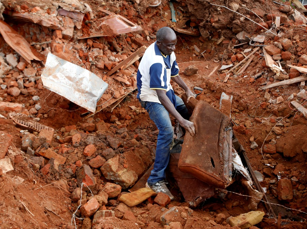 Homem procura por documentos em meio a escombros após passagem de ciclone no Zimbábue — Foto: REUTERS/Philimon Bulawayo