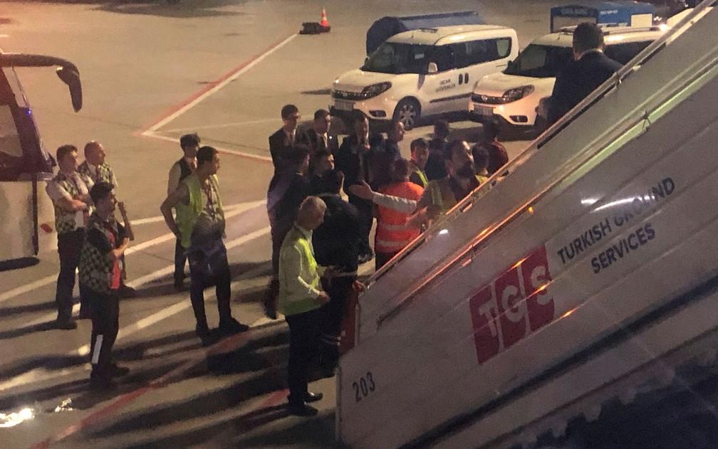 Escoltado por seguranças e policiais, passageiros desembarca em Istambul após provocar tumulto em voo da Turkish Airlines entre Istambul e Cartum, na sexta-feira (14) — Foto: AP Photo/Hussein Malla