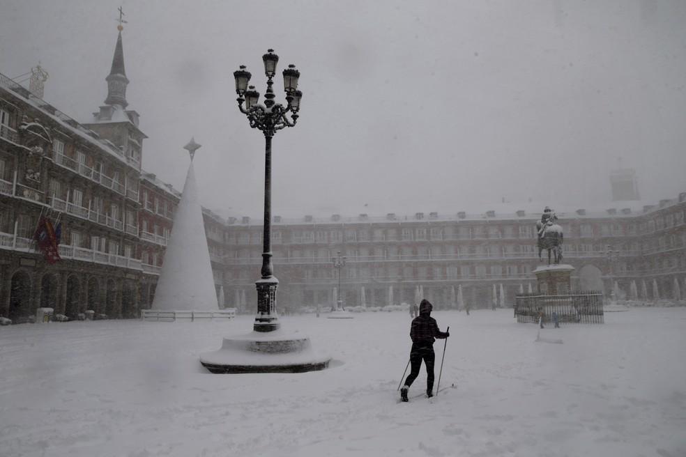 Uma mulher esquia ao cruzar a Plaza Mayor em Madrid durante uma forte nevasca em Madrid, Espanha, sábado, 9 de janeiro de 2021 — Foto: Andrea Comas/AP Photo