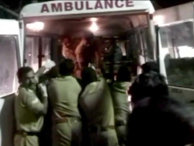 Policiais levam feridos para uma ambulância após incêndio e explosão em templo na Índia (Foto: ANI / via Reuters)