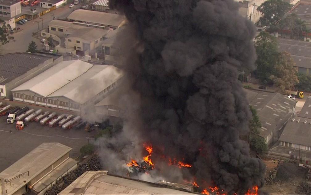 Incêndio atinge pneus ao lado de galpão (Foto: Reprodução/TV Globo)