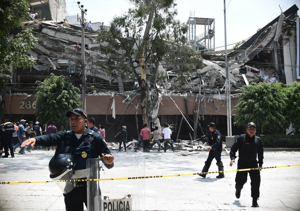 Policiais fazem cordão de isolamento em volta de prédio que desabou durante forte tremor que atingiu a Cidade do México nesta terça-feira  (Foto: Ronaldo Schemidit / AFP )