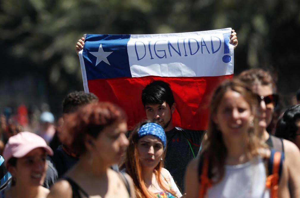 Manifestante com bandeira do Chile pede 'dignidade!' em protesto em Santiago nesta quinta-feira (24)  — Foto: Henry Romero/Reuters