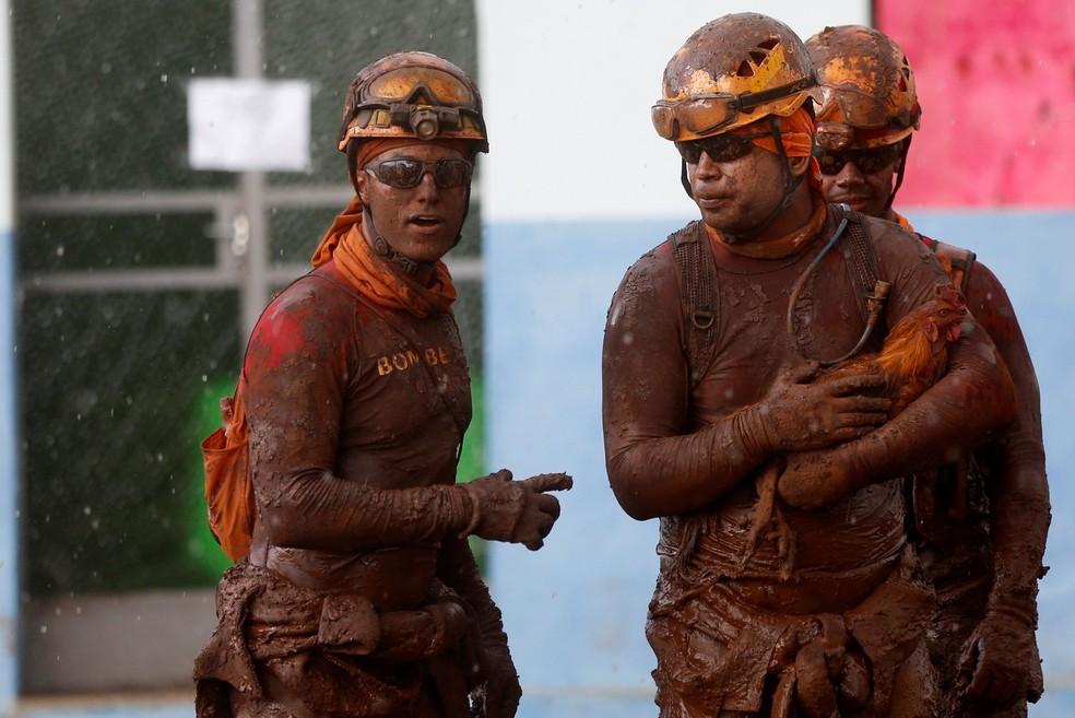 Bombeiro sujo de lama segura galo resgatado da lama em Brumadinho, após rompimento de barragem da Vale — Foto:  Adriano Machado/Reuters